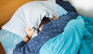 teen hiding head under pillow